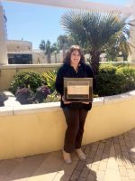 Rita Lyons, graphic arts technician at West Virginia Northern Community College, holds the Paragon Award she received from the National Council for Marketing and Public Relations for a billboard she designed on the college's cyber security program. She received the award during the annual NCMPR conference held this year in Charleston, South Carolina.
