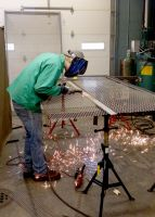 Ian Minor, of Moundsville and a senior student in welding at West Virginia Northern Community College, works on a section of a cage in a community service partnership with CHANGE, Inc., in Weirton.